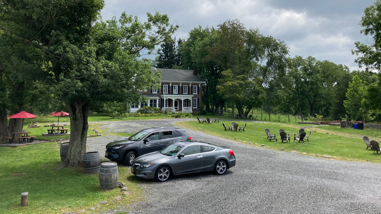 Gravel parking lot with 2012 Honda Accord coupe and Toyota SUV. A large mansion is on the other end of the lot.