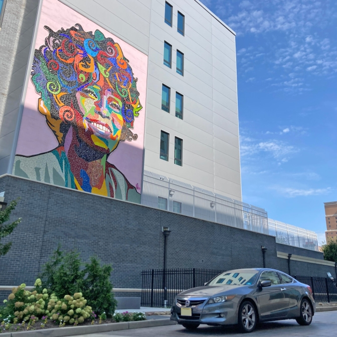 2012 Honda Accord parked beneath mosaic mural of Whitney Houston on side of building.
