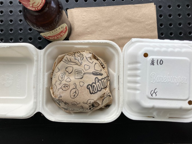 Burger in wax paper wrapping, box with fries, and a ginger beer bottle on metal table.