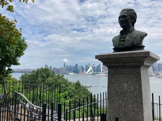 Bust of Alexander Hamilton overlooking Hudson River and Manhattan skyline in distance.