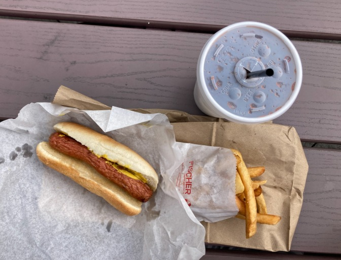 Hot dog, fries, and birch beer in cup, on wooden table.