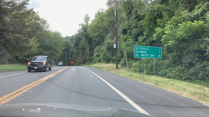 Sign along two-lane road that reads BUTTZVILLE 1, DELAWARE 7, DEL WATER GAP 14