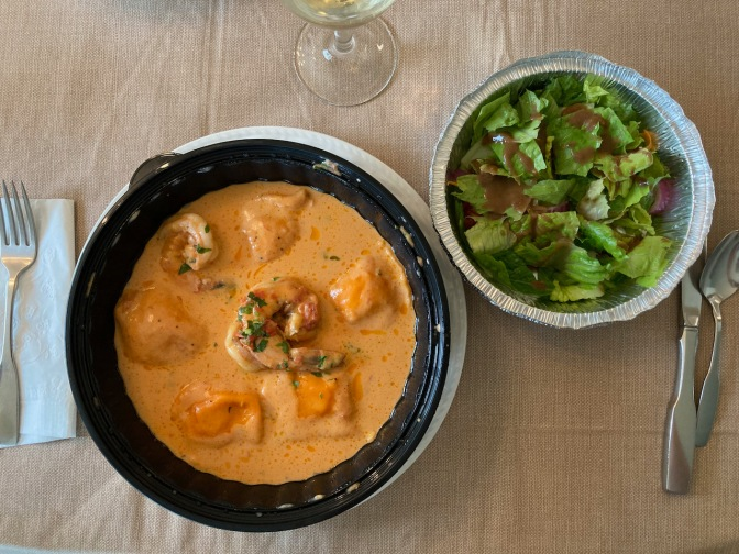 Plate with lobster ravioli, beside bowl with salad.
