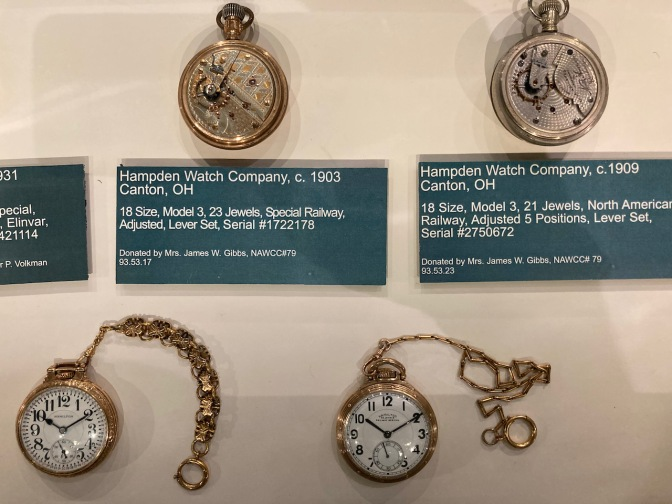 Four pocket watches in display case, two front-facing and two with their rear movements opened.