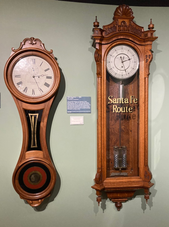 Two railway clocks on wall, one of which says SANTA FE ROUTE.