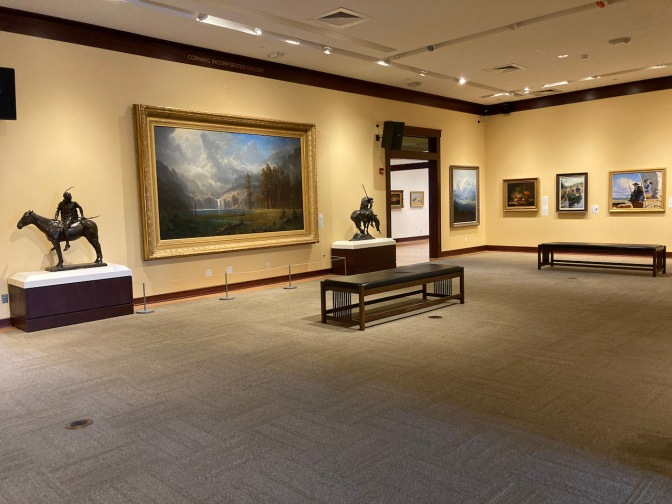 Gallery of American art with paintings hung around room.