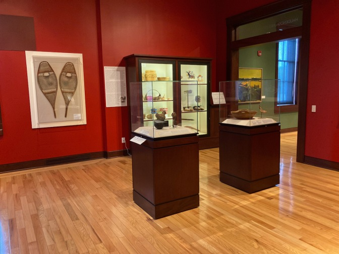 Gallery with Native American items, including baskets, jars, and snow shoes.
