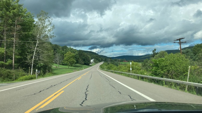 View of twisty road through farmland and mountains.