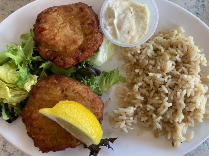 White plate with crab cakes, rice, and tartar sauce.