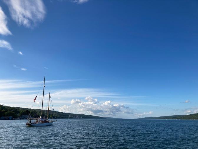 View of Seneca Lake, with sailboat on the lake, heading north.