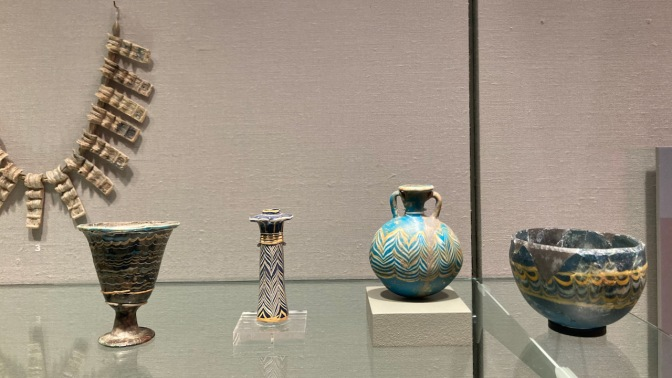 Egyptian glass items, including small vases and a necklace.