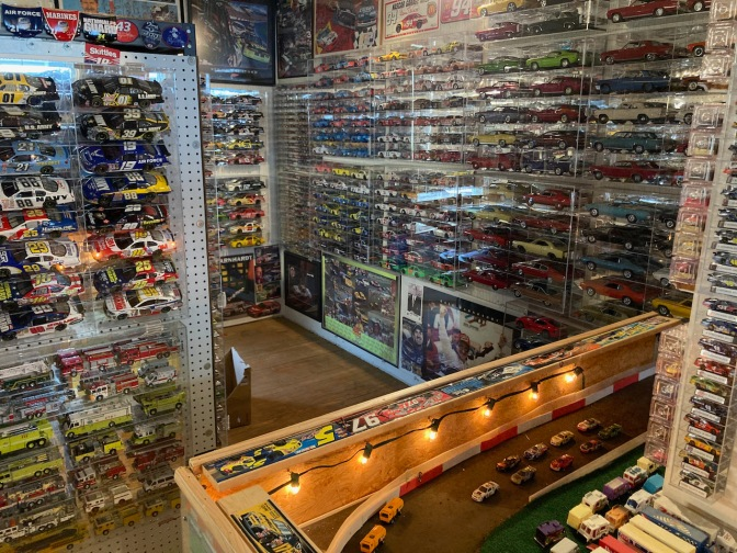 Toy die cast cars in racks on walls.