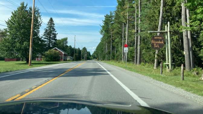 View of I-28, with sign on right saying ENTERING ADIRONDACK PARK.