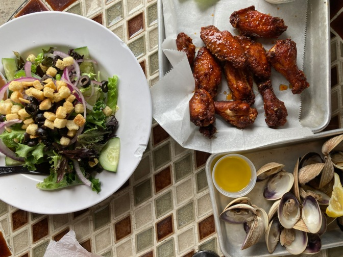 Plate with salad, tray with clams, and tray with chicken wings.