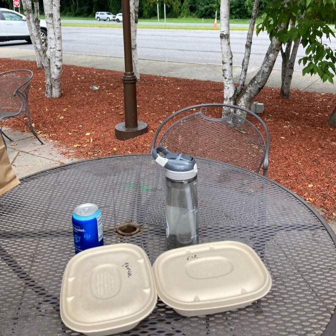 Two boxes of food on metal table at rest stop.