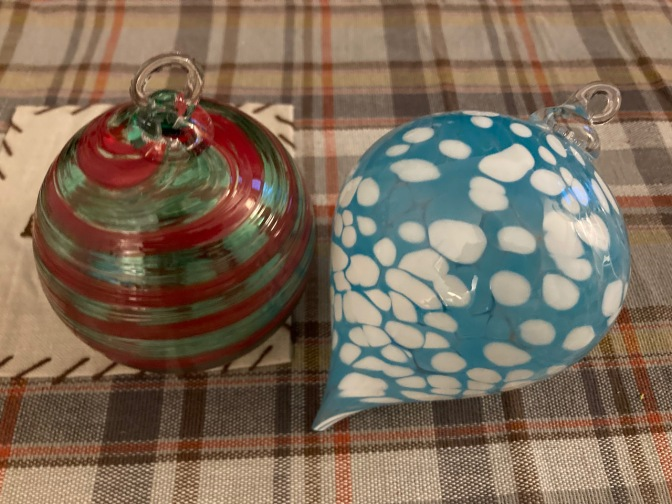 Two Christmas ornaments, one blue and white, one green and red, on plaid tablecloth.