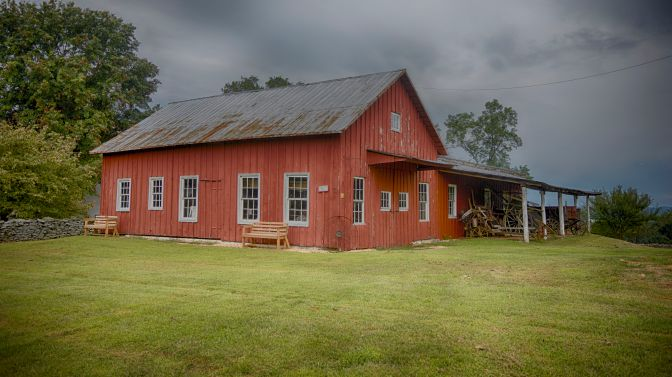 Blacksmith shop, in red wood, in field.