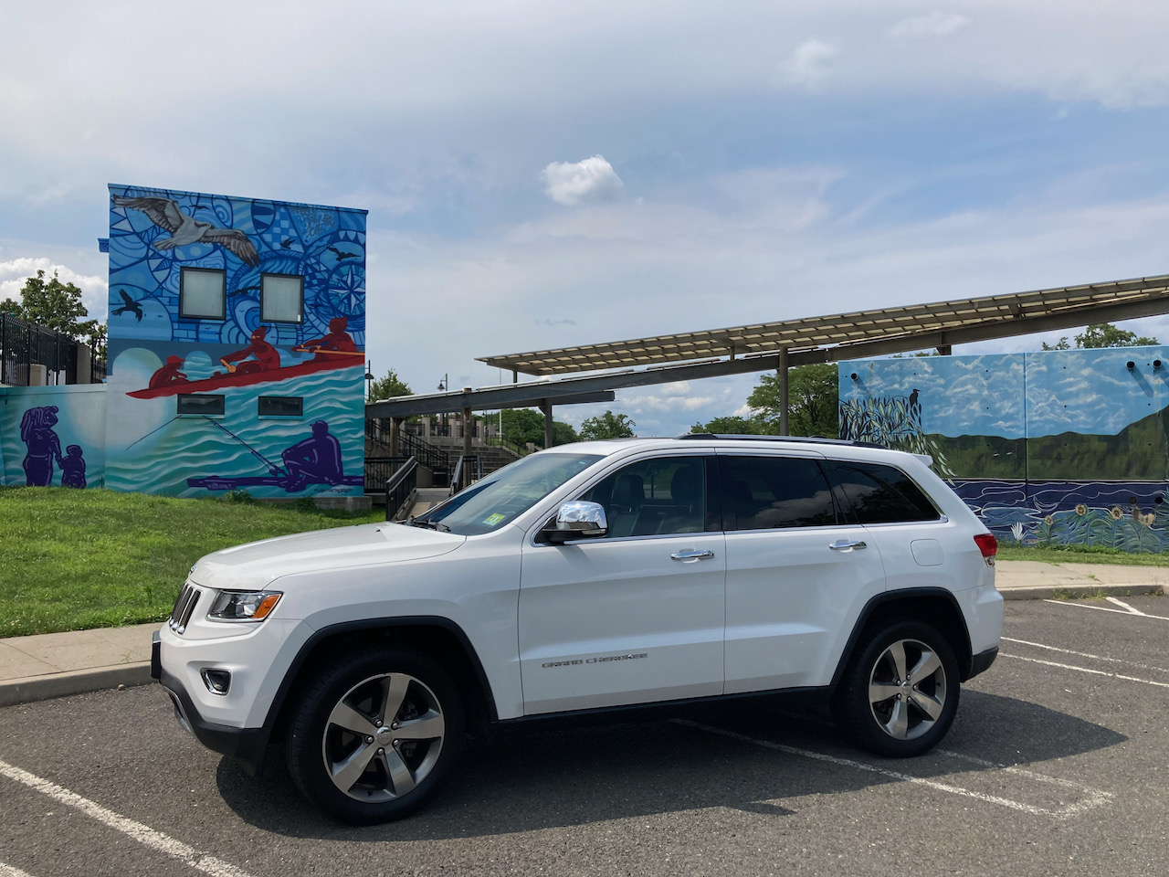 2014 Jeep Grand Cherokee parked in front of Raritan River Ways mural in public park.