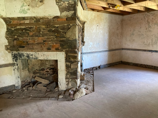 Interior of stone house, with original fireplace.