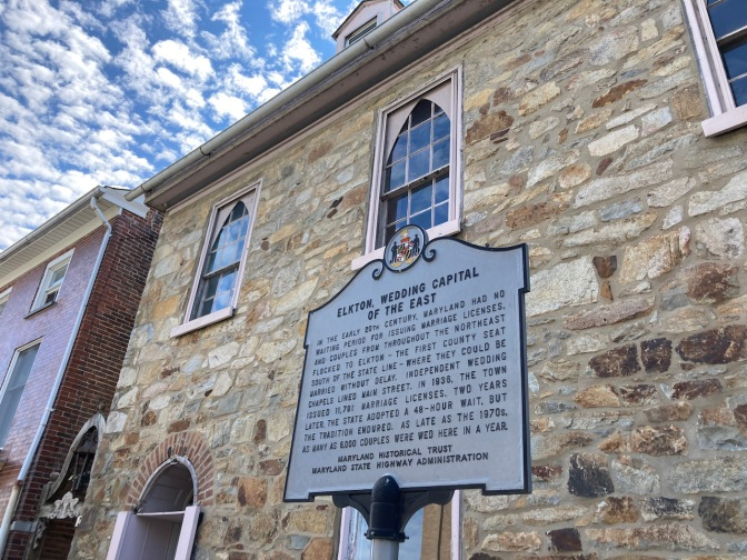 Exterior of stone building, with sign in front telling history of quick wedding chapels in Elkton.