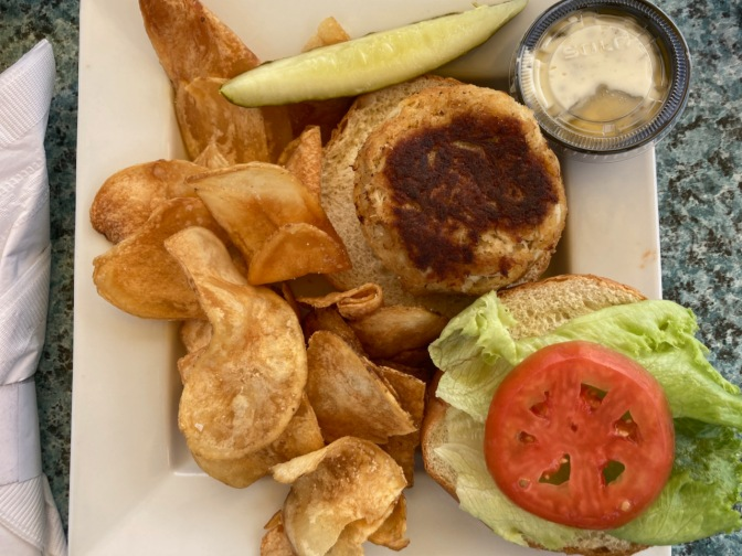 Crab cake sandwich on bun, with potato chips and pickle, on white plate.