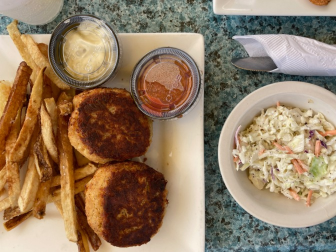Crab cakes on plate with french fries, alongside a bowl of coleslaw.
