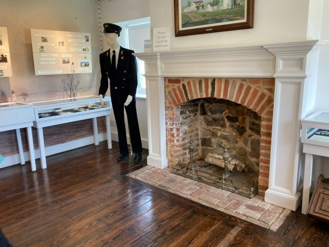 Mannequin dressed as lighthouse keeper, beside fireplace, in museum.
