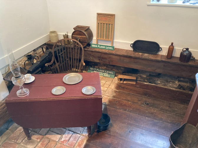 Kitchen, with two different floor levels - 1827 and 1884. Kitchen furnishings and a small dining table are in the room.