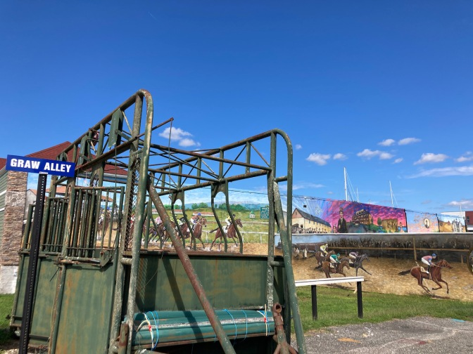 Starting gate, and murals of racetrack.
