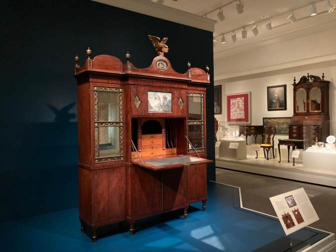 Large wooden secretary in museum gallery of furniture.