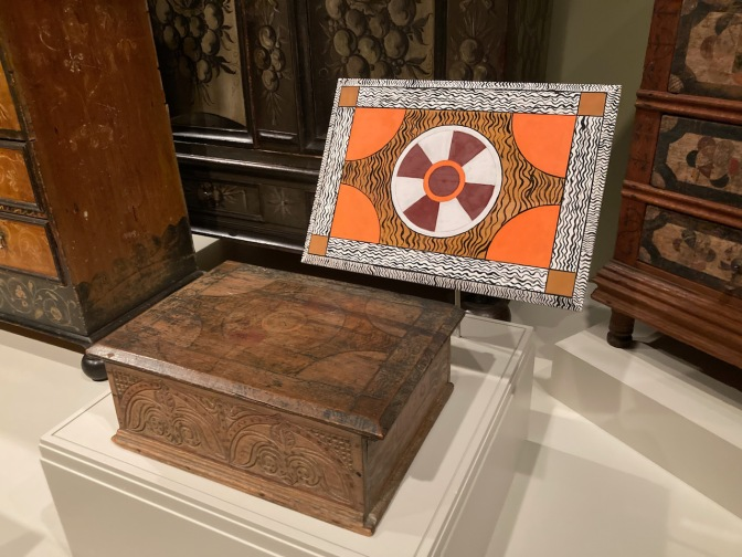 Wooden box, with elaborately painted lid on display beside it.