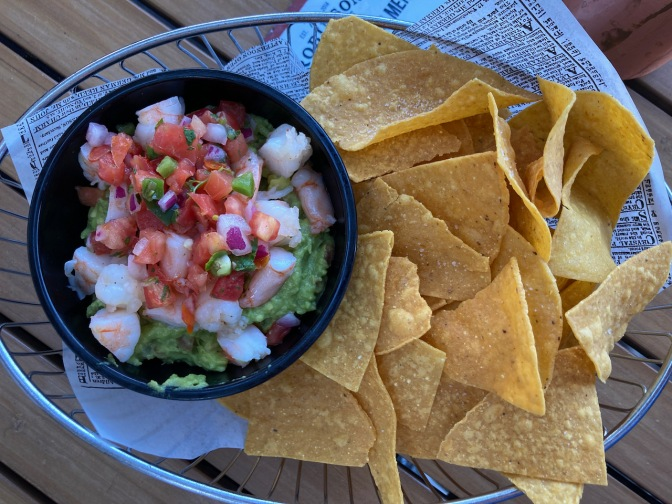 Tortilla chips in basket, with bowl of guacamole and shrimp.