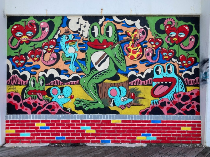 Mural of cartoon frogs and apples on wall.