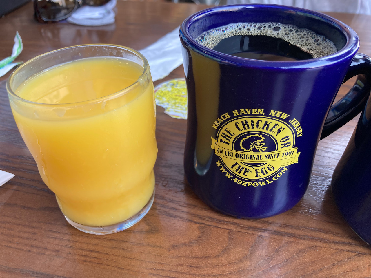 Glass of orange juice and cup of coffee on table.