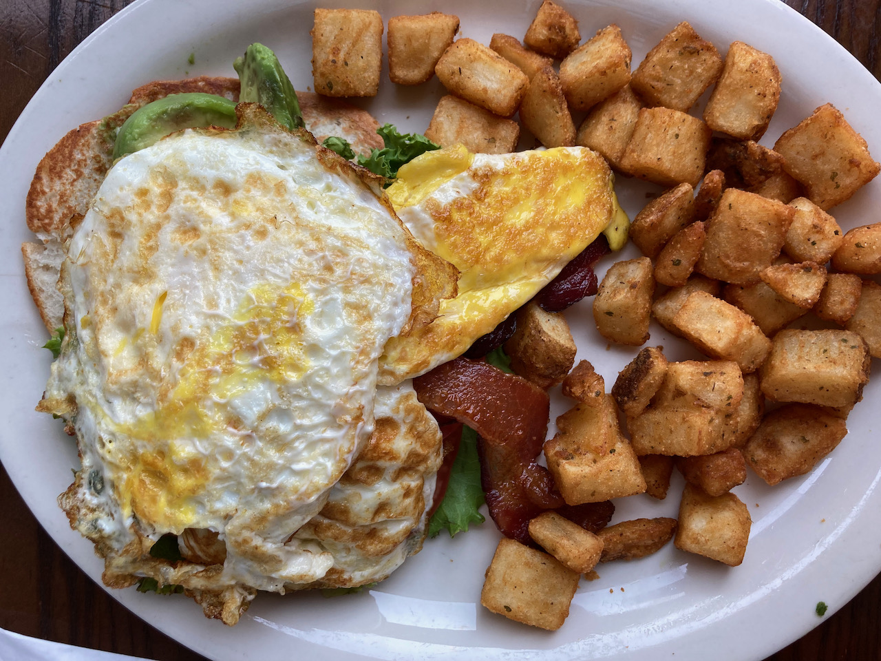 Egg and avocado on toast, with bacon and home fries.