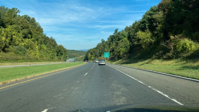 View of Route 23 northward. The road is tree-lined, and mountains are in the distance.