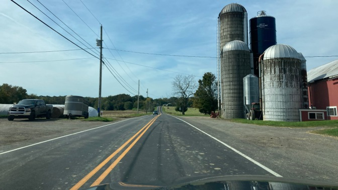 Farm with silos on right side of road, along two-lane country road.