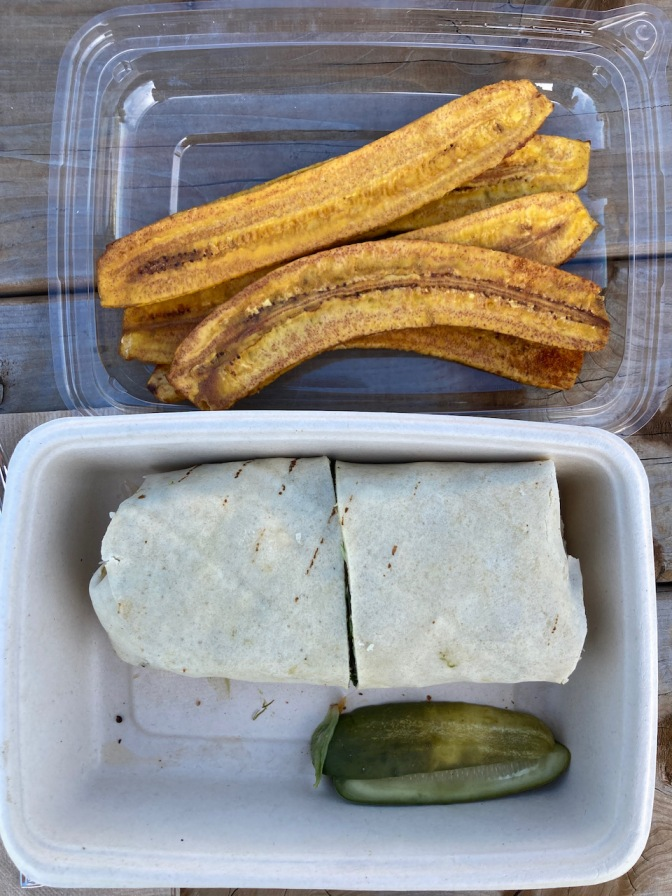 Chicken salad wrap with pickles and plantain chips in plastic container.