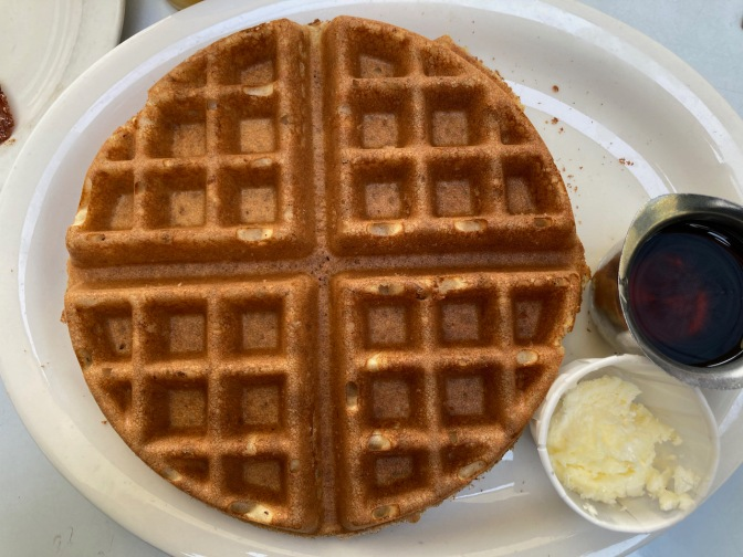 Gluten-free waffle on plate with maple syrup and butter.