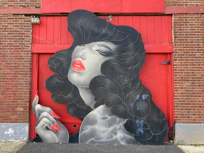 Mural of woman in front of brick wall.