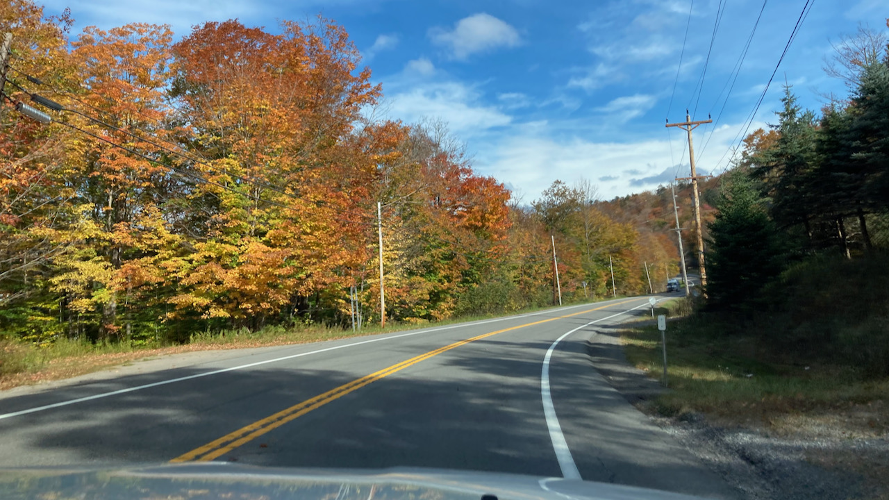NY28 with red and orange trees along side of road.
