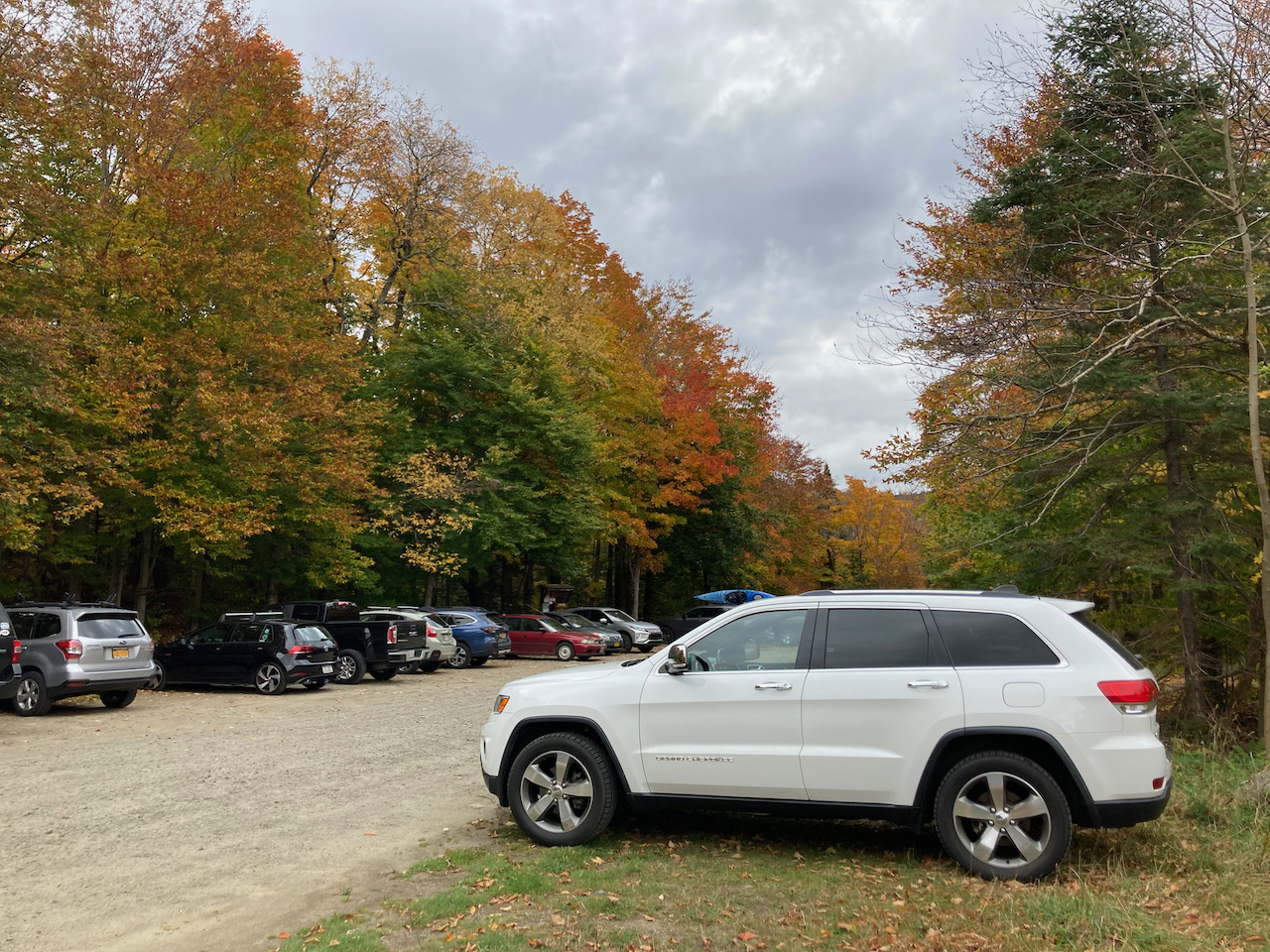 White Jeep Grand Cherokee, parked in dirt lot of Blue Mountain hiking trail.