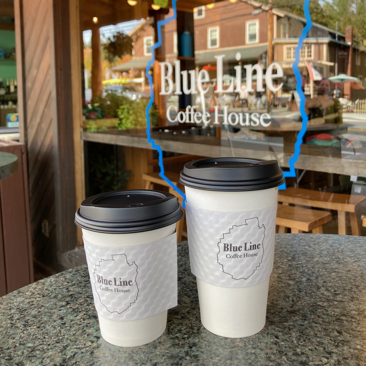 Two coffee cups on table in front of window. Window has Blue Line Coffee House decal.