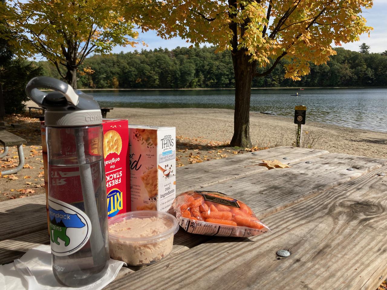 Picnic table with food, on banks of Lake Moreau.