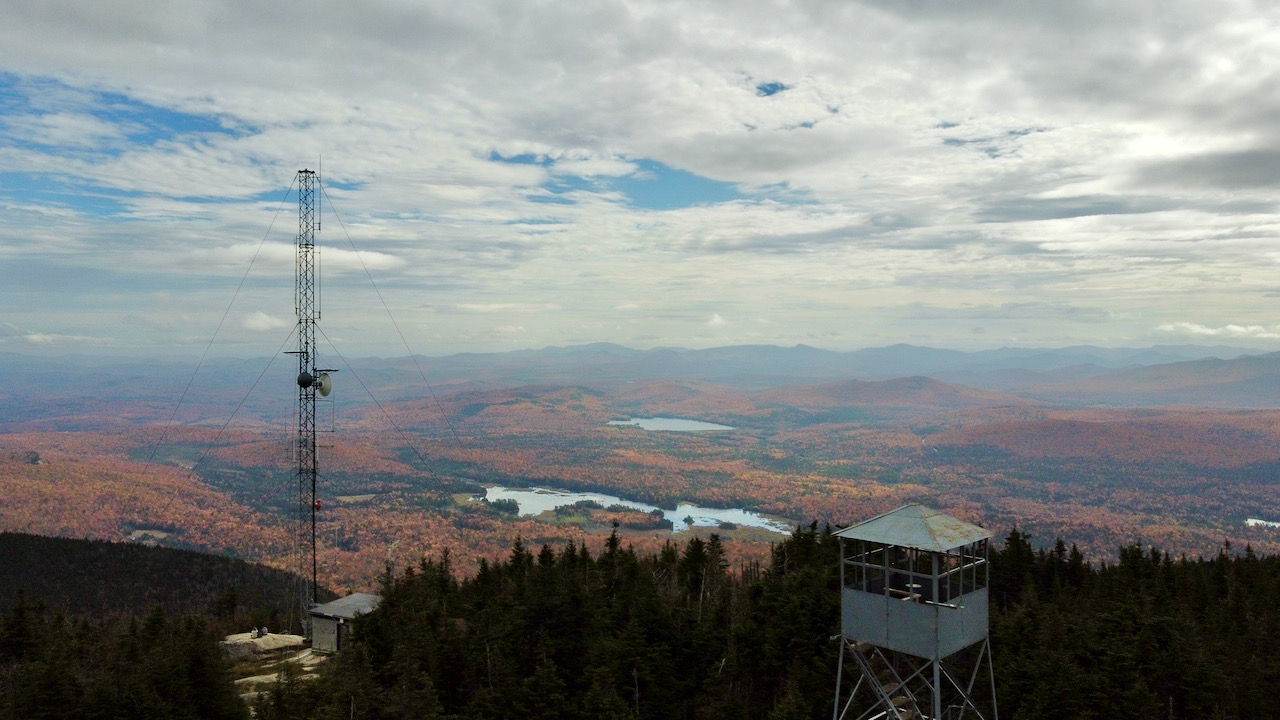 View of fire tower and wireless antenna in foreground, and mountains in background.